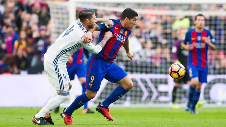 Luis Suárez, protegiendo el balón del acecho de Sergio Ramos