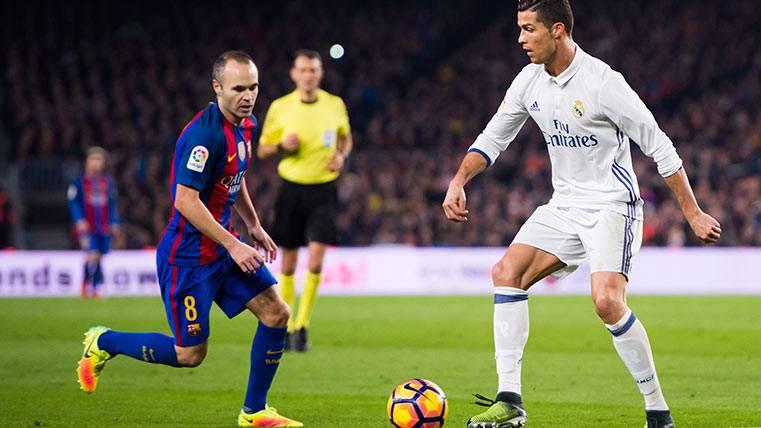 Andrés Iniesta en el último Clásico ante el Madrid, luchando por un balón con CR7
