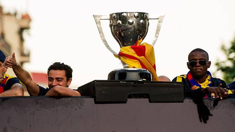Éric Abidal, junto a Xavi Hernández celebrando un título del Barça