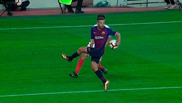 Jordi Alba, desviando un balón con el brazo extendido en el área del Barça
