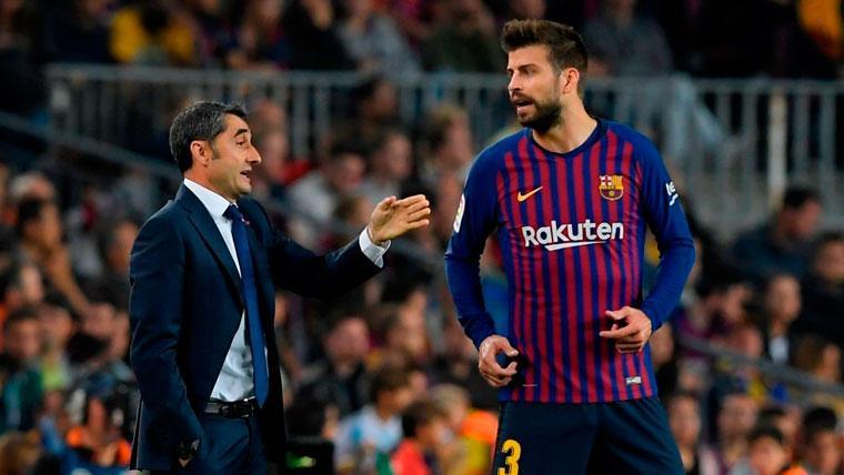 Ernesto Valverde y Gerard Pique conversan durante un partido del FC Barcelona